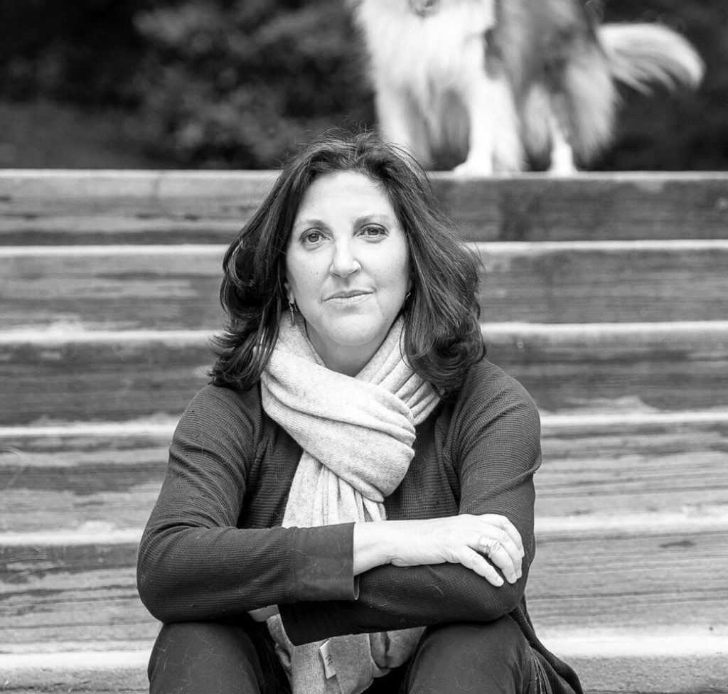 Image of Author Laura Zigman sitting on steps with a blurry dog in the background