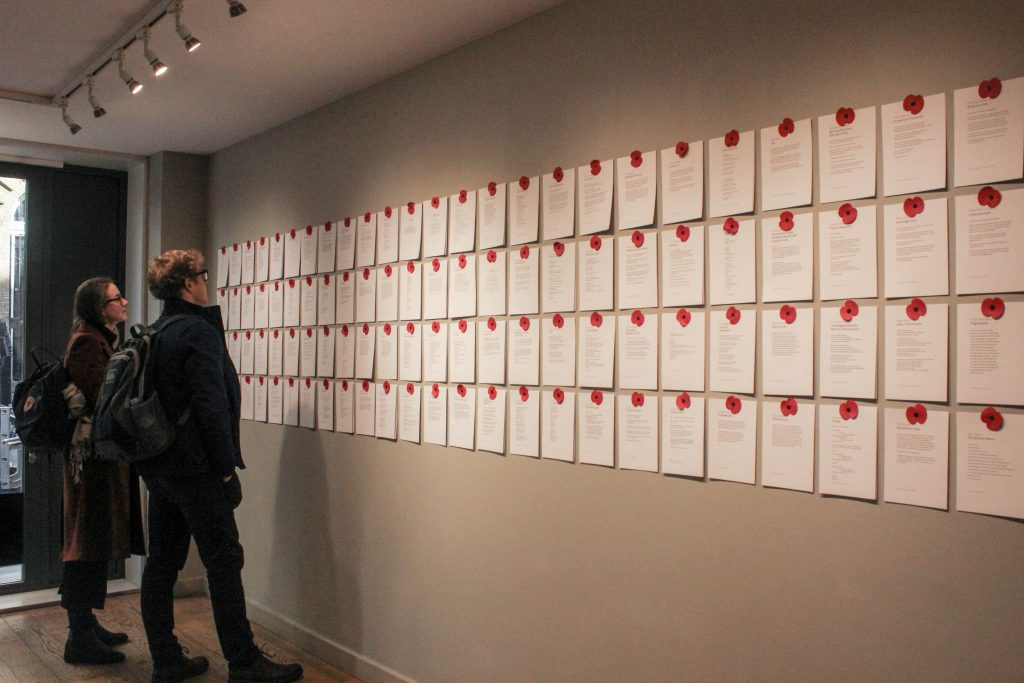 People reading poems from the armitice project which are written on paper pinned to wall by red poppies.